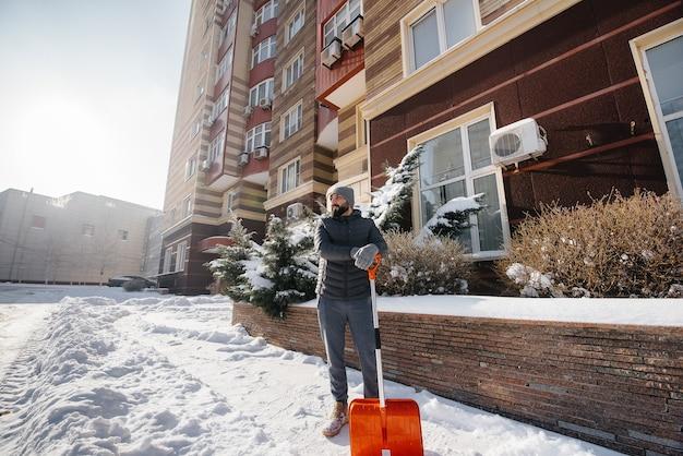 Un giovane spazza la neve davanti alla casa in una giornata di sole e gelo.