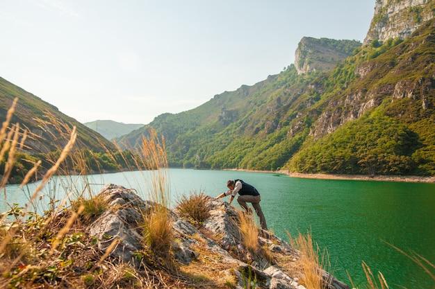Giovane uomo che si arrampica accanto a un bellissimo fiume azzurro sotto incredibili rocce di montagne