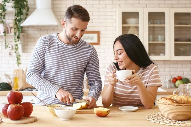 Giovane che cucina la colazione per la sua amata fidanzata in cucina