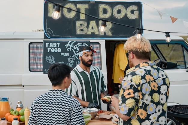 Giovane che cucina e vende hot dog ai giovani mentre stanno in piedi all'aperto