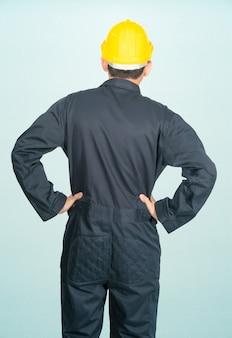 Giovane uomo in tuta casco elmetto protettivo isolato su sfondo blu