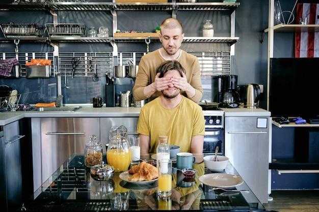 Giovane che copre gli occhi di suo marito con le mani vicino al tavolo della cucina