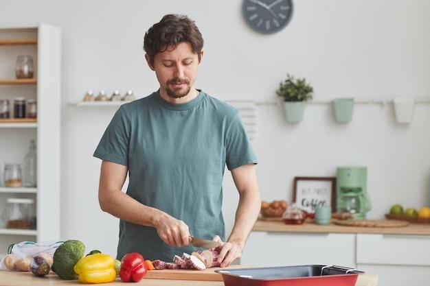Giovane che taglia le verdure fresche sul tagliere che prepara la cena a casa