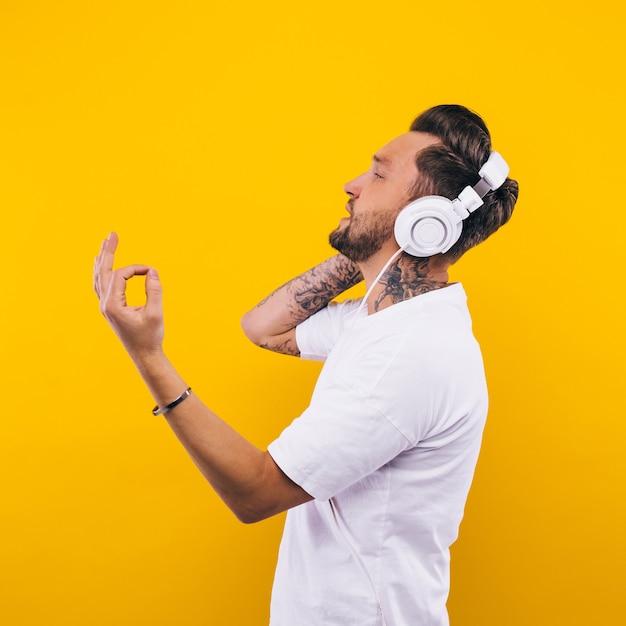 Giovane che balla e ascolta musica. emozioni, espressioni facciali, sentimenti, linguaggio del corpo, segni. immagine su uno sfondo giallo studio.