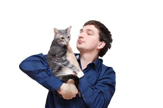Giovane uomo in camicia blu scuro che tiene gatto grigio nelle mani.