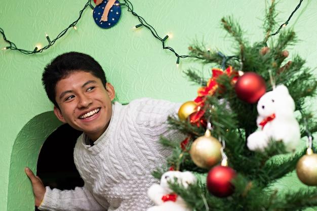 Un giovane che decora l'albero di natale a casa dei suoi nonni