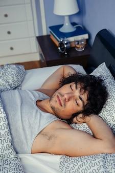 Giovane uomo profondamente addormentato nel letto di casa