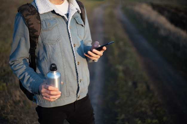 Giovane uomo in giacca di jeans con smartphone e bottiglia di alluminio nelle sue mani