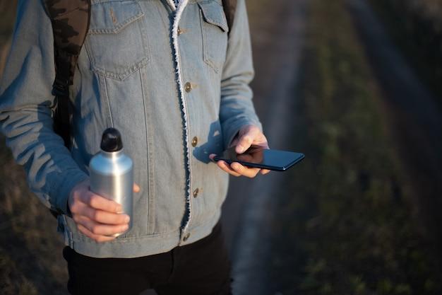 Giovane uomo in giacca di jeans con smartphone e bottiglia di alluminio nelle sue mani Foto Premium