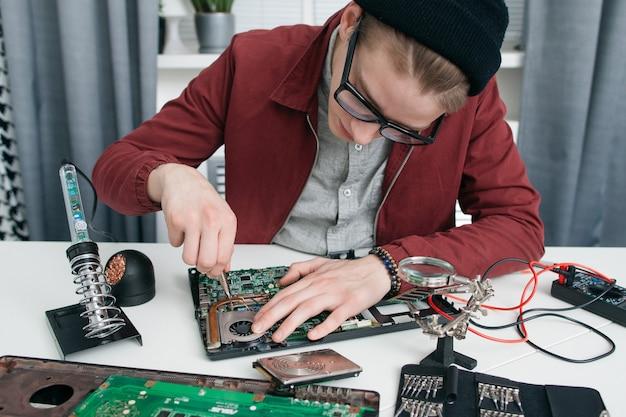 Giovane uomo smontaggio scheda madre del computer.