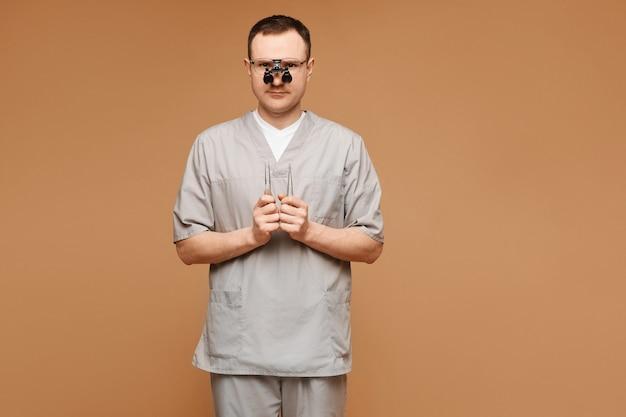 Il giovane medico in uniforme medica e occhiali mantiene gli strumenti del chirurgo nelle mani e in posa sullo sfondo beige, isolato. assistenza sanitaria e concetto di emergenza.