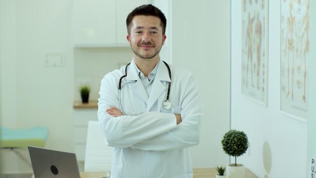 Il medico del giovane indossa l'uniforme medica bianca e lo stetoscopio che esaminano macchina fotografica, faccia felice del medico professionista maschio che posa per il ritratto di vista ravvicinato al lavoro in ospedale.