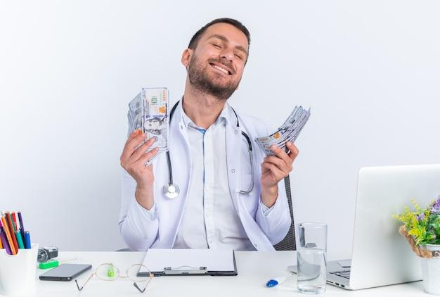 Giovane medico in camice bianco e con lo stetoscopio che tiene contanti felice ed eccitato seduto al tavolo con il computer portatile su sfondo bianco