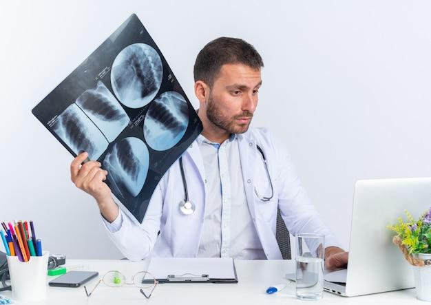 Giovane medico in camice bianco e con stetoscopio che tiene i raggi x guardando lo schermo del suo laptop seduto al tavolo su bianco