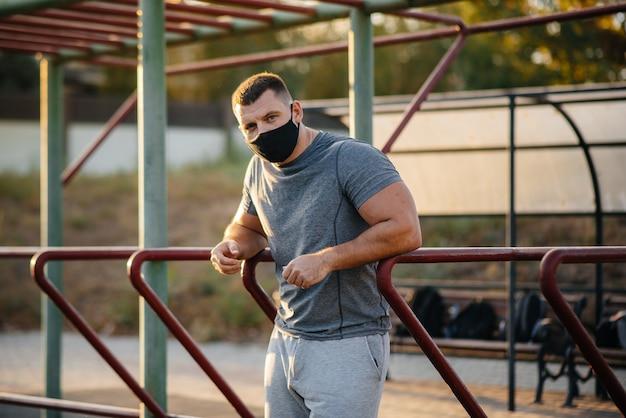 Un giovane fa flessioni su un campo sportivo con una maschera durante una pandemia al tramonto