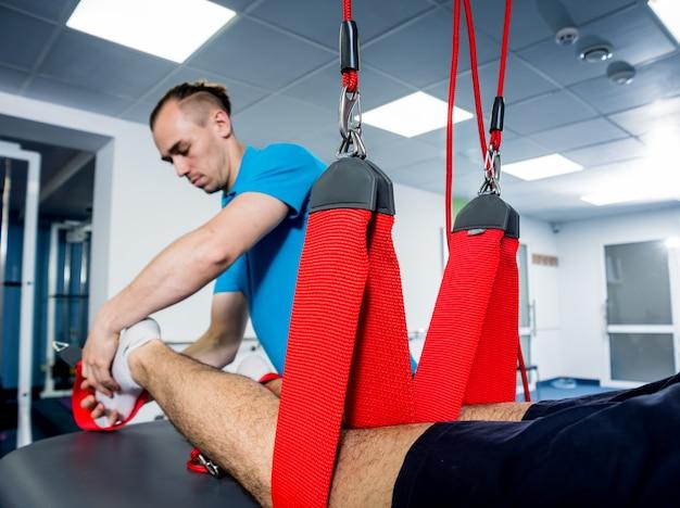 Giovane che fa terapia di trazione fitness con sistema di allenamento basato su sospensione.