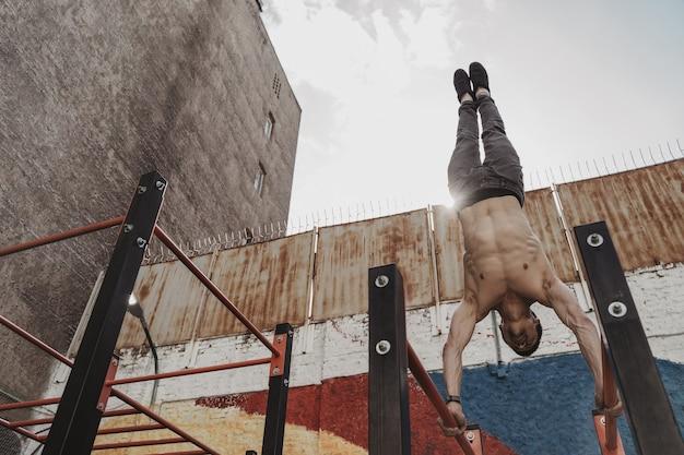 Giovane uomo che fa mano stand push up esercizio su barre parallele