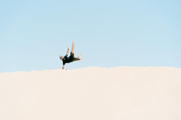 Giovane che fa verticale nelle dune di sabbia concetto di vacanze e libertà