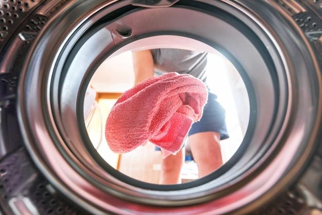 Giovane che fa vista lavanderia dall'interno della lavatrice
