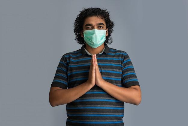 Giovane che fa namaste a causa dello scoppio di covid-19. nuovo saluto per evitare la diffusione del coronavirus invece di salutare con un abbraccio o una stretta di mano. pratica yoga per l'equilibrio mentale.