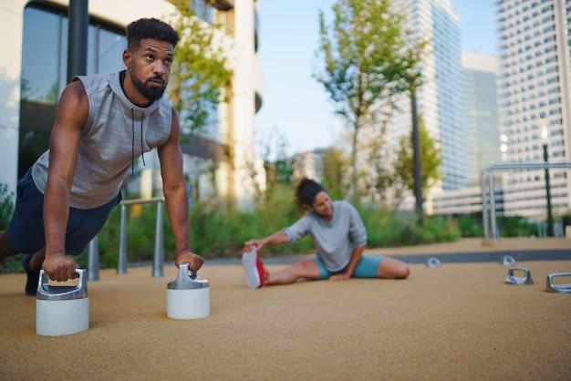 Giovane che fa flessioni all'aperto in città, esercizio di allenamento e concetto di stile di vita sano.