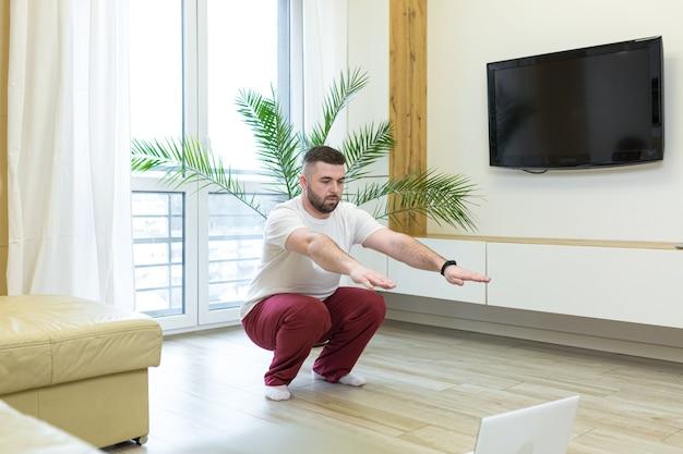Giovane che fa yoga a casa con il computer portatile