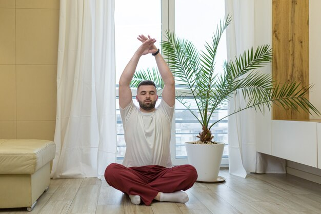 Giovane che fa yoga a casa