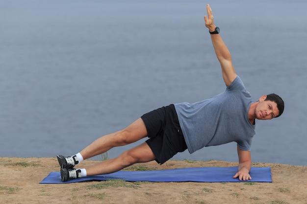Giovane che fa yoga all'aperto in un ambiente naturale
