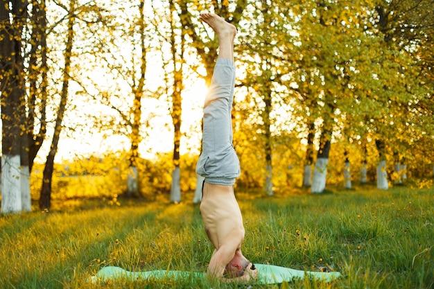 Giovane che fa yoga nel parco al tramonto. uno stile di vita sano