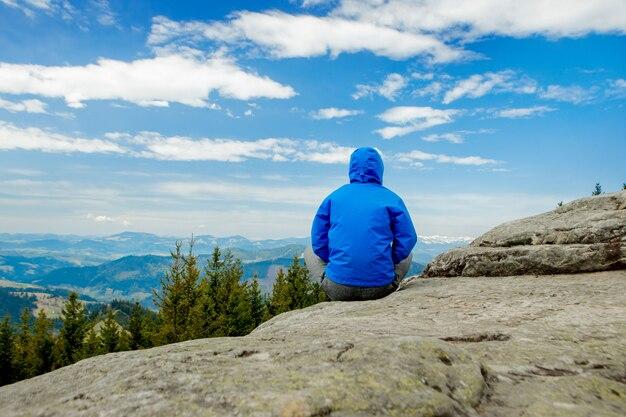 Giovane che fa yoga in un posto meraviglioso della montagna, nuova era, energia, meditazione e salute, giovane che sorride durante la posizione di loto.