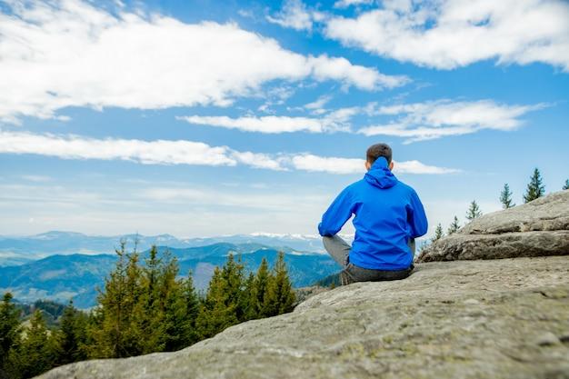 Giovane che fa yoga in un meraviglioso luogo di montagna, new age, energia, meditazione e salute, giovane uomo sorridente durante la posizione del loto.