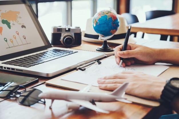 Giovane uomo disegna mappe per la pianificazione del turismo viaggio di vacanza. viaggio, viaggio vacanza,