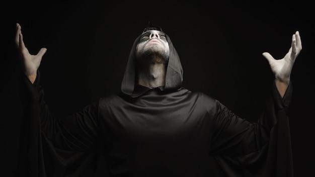 Giovane uomo vestito come angelo delle tenebre per halloween su sfondo nero.