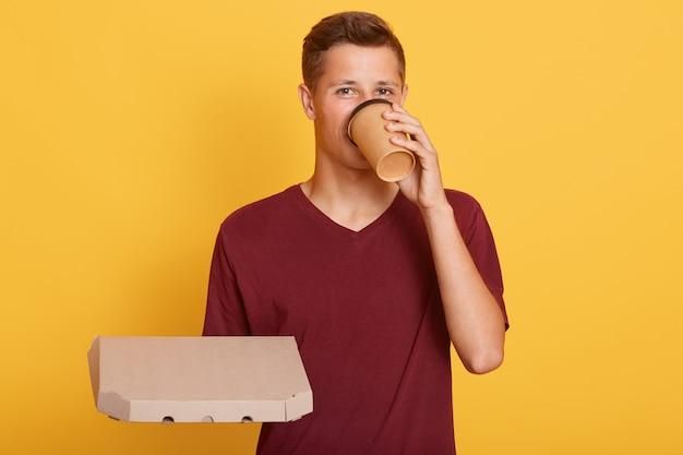 Giovane che beve caffè e che tiene grande pizza in mano