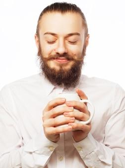 Il giovane che beve una tazza di caffè o di tè ha isolato il fondo bianco