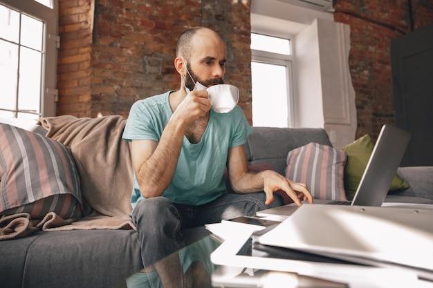Giovane che beve il tè a casa mentre lavora