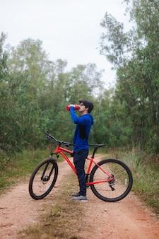 Acqua potabile del giovane sulla sua bici su una strada forestale, stile di vita attivo.