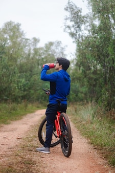 Giovane uomo che beve acqua sulla sua bici su una strada forestale, praticando sport nella natura, stile di vita attivo.