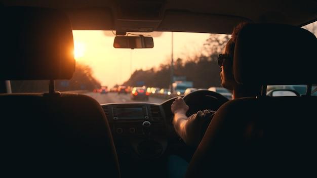 Il giovane alla guida dell'auto lungo l'autostrada della città