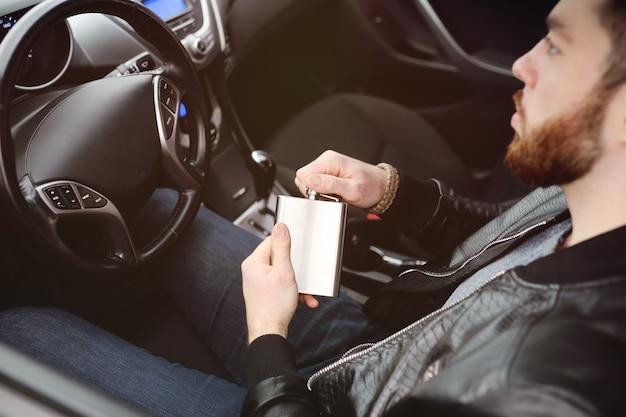 Giovane uomo alla guida di un'auto con un pallone di ferro con alcool. cattiva abitudine. guidatore ubriaco.