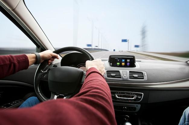 Il giovane alla guida di un'auto moderna su strada asfaltata