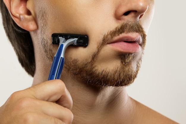 Giovane durante la routine di rasatura con un rasoio di sicurezza
