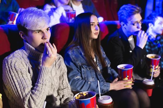 Il giovane mangia popcorn al cinema e guarda un film