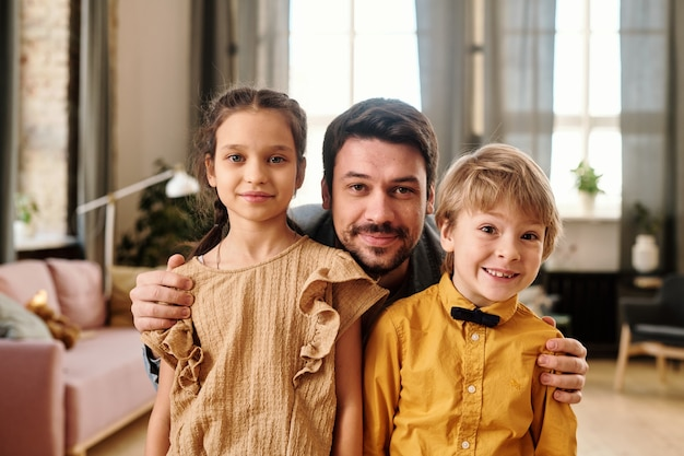 Giovane che abbraccia i suoi due bambini carini