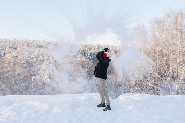 Un giovane si gode una giornata invernale sullo sfondo di un bosco innevato