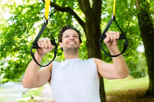Giovane che si esercita con l'imbracatura dell'istruttore della sospensione nel parco della città sotto gli alberi di estate per il fitness sportivo