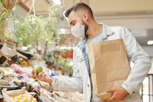 Giovane uomo in maschera facciale che tiene il sacchetto di carta e la scelta di frutta durante l'acquisto di generi alimentari freschi al mercato biologico