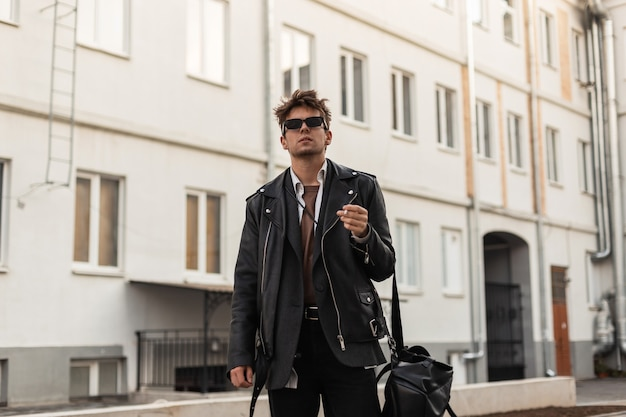 Giovane in vestiti di pelle nera oversize della gioventù di moda con stand zaino con sigaretta vicino agli edifici della città in una giornata primaverile. brutal guy hipster in occhiali da sole scuri si diverte a fumare all'aperto