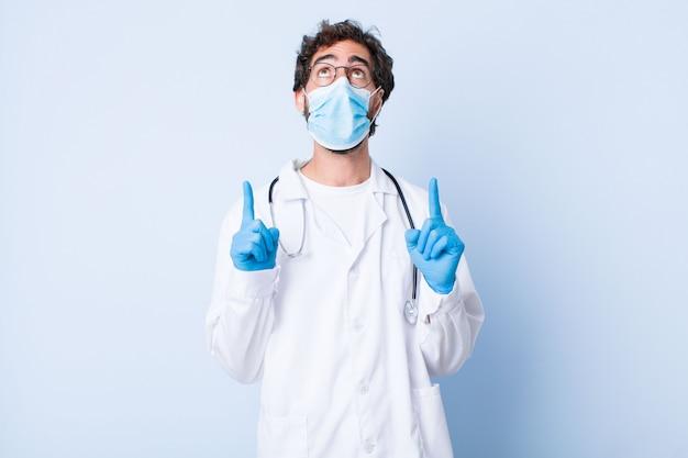 Giovane che si sente stupito e con la bocca aperta rivolto verso l'alto con uno sguardo scioccato e sorpreso. concetto di coronavirus