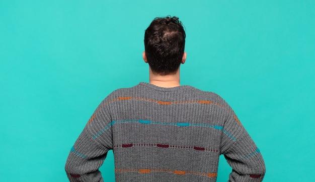 Giovane che si sente confuso o pieno o dubbi e domande, chiedendosi, con le mani sui fianchi, vista posteriore